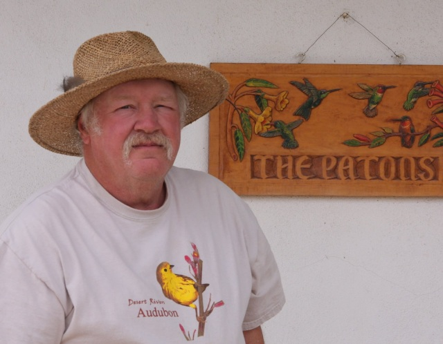"Larry Morgan, ""Ambassador For The Birds,"" for Paton's Birder Haven, stands in front of ""The Paton's"" sign  that hangs at the entrance of the Paton's house in Patagonia AZ. Photo taken by ©Walter Andrew. All Rights Reserved. Photo may not be used without written permission. Please respect the wishes of the Paton Family."